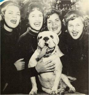 Four girls try to match the mascot's smile in this shot from 1956.